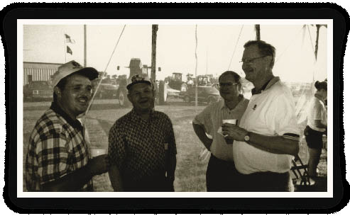 Allen Rider, vice president of New Holland North American Agriculture (rt), shares a coffee with some new combine owners during a New Holland dealer open house (circa 2000). He says his best dealers learned that the first step in selling a new combine was to have a customer waiting to buy the ones they were trading in.