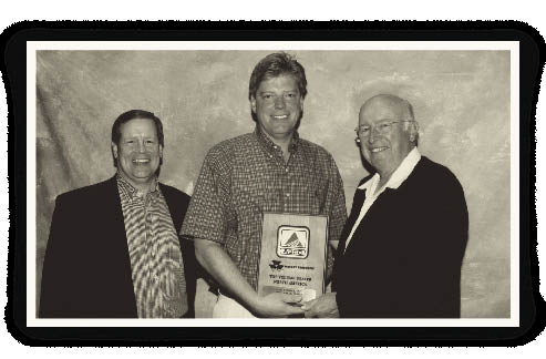 Don Millard of AGCO, and Cleve Buttars (ctr), owner of Agri-Service, accepts top volume dealer award for 2004 from Bob Ratliff, chairman and CEO of AGCO Corp.