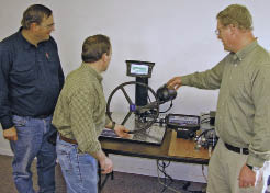 Keep in mind that everyone learns differently and at different paces. Alternating between talks, hands-on presentations and handouts ensures everyone will get a good grasp on the content. Here, a Binkley & Hurst technician demonstrates the guidance system for the planter to two customers.