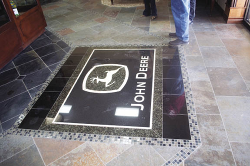 A custom-made John Deere logo made of black and green granite and yellow onyx is inlaid into the slate-top floor that's used throughout the showroom.