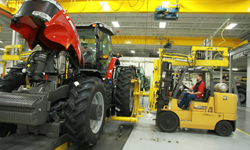 A rear wheel is installed on a Massey Ferguson 8600 Series row crop tractor at AGCO's newly expanded manufacturing facility in Jackson, Minn.
